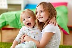 Petites filles ou soeurs heureuses étreignant à la maison Photographie stock