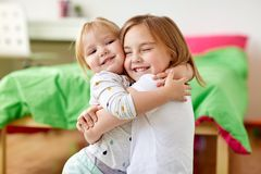 Petites filles ou soeurs heureuses étreignant à la maison Images stock
