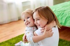 Petites filles ou soeurs heureuses étreignant à la maison Image libre de droits