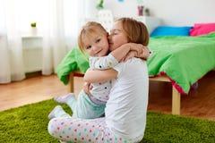 Petites filles ou soeurs heureuses étreignant à la maison Photographie stock libre de droits