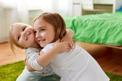 Petites filles ou soeurs heureuses étreignant à la maison Images libres de droits