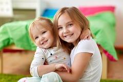 Petites filles ou soeurs heureuses étreignant à la maison Photos libres de droits
