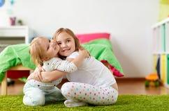 Petites filles ou soeurs heureuses étreignant à la maison Photo stock