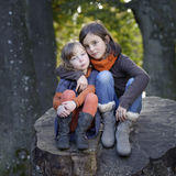 2 petites filles s'asseyant sur un tronc Photo stock