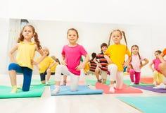 Petites filles se tenant sur le genou dans la classe de forme physique Photographie stock libre de droits