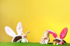 Petites filles utilisant des bandeaux d'oreilles de lapin et jouant avec des lapins de Pâques de jouet sur la surface d'herbe ver photo stock