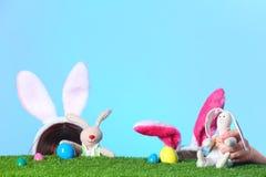 Petites filles utilisant des bandeaux d'oreilles de lapin et jouant avec des lapins de Pâques de jouet sur la surface d'herbe ver photos stock