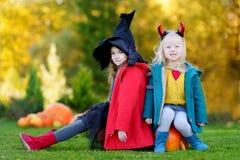 Petites filles utilisant le costume de Halloween sur une correction de potiron Images stock