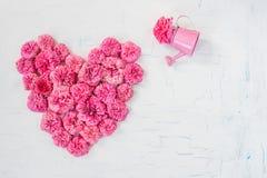 Petites fleurs roses des roses sous forme de coeur sur un fond criqué blanc Photos libres de droits