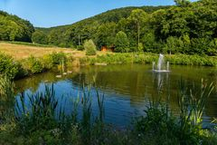 Petites fontaines au milieu d'un lac dans une pelouse près de hautes montagnes vertes photos stock