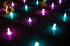 Petites fontaines rougeoyant dans l'obscurité dans différentes couleurs images stock