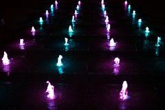 Petites fontaines rougeoyant dans l'obscurité dans différentes couleurs image libre de droits