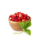 Petites fraises sauvages dans une cuvette en bois avec des feuilles Photos libres de droits
