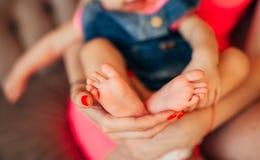 Petites jambes de l'enfant, mensonges sur les mains des parents Newb Photographie stock libre de droits