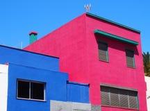 Petites maisons en béton modernes roses et bleues angulaires en Espagne Photo stock