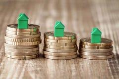 Petites maisons vertes sur les pièces de monnaie empilées Photographie stock