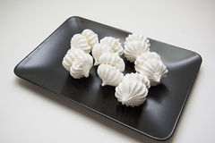 Petites meringues de plat noir Photographie stock