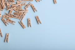 Petites pinces à linge en bois mignonnes sur un fond bleu photo libre de droits