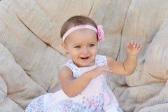 Petites poses de bébé sur une chaise blanche Elle sourit heureusement photos libres de droits