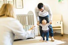 Petites premières étapes de bébé avec l'aide de parent photographie stock libre de droits