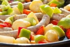 Petites saucisses, pommes de terre et tomates dans une casserole chaude faisant cuire dehors au soleil Image libre de droits