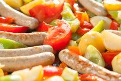 Petites saucisses, pommes de terre et tomates faisant cuire dans une casserole chaude coooking dehors au soleil Photo libre de droits