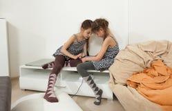 Petites soeurs à l'aide du comprimé dans la chambre à coucher Photographie stock libre de droits