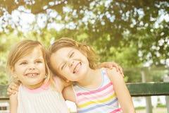 Petites soeurs étreignant et souriant Images stock