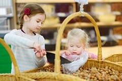 Petites soeurs achetant des noisettes de stock de nourriture Photos stock
