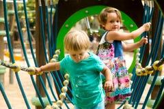 Petites soeurs au terrain de jeu en parc Photos libres de droits
