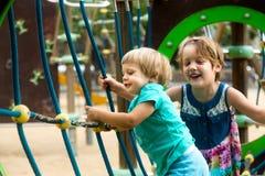 Petites soeurs au terrain de jeu en parc Photographie stock libre de droits