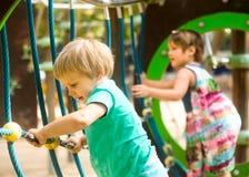 Petites soeurs au terrain de jeu en parc Photo stock
