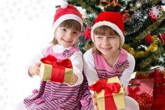 Petites soeurs avec des cadeaux sous l'arbre de Noël Images libres de droits