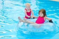 Petites soeurs ayant l'amusement dans une piscine Image libre de droits