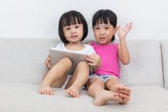 Petites soeurs chinoises asiatiques à l'aide du comprimé Photographie stock