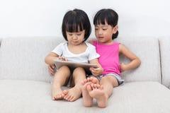 Petites soeurs chinoises asiatiques à l'aide du comprimé Photo libre de droits