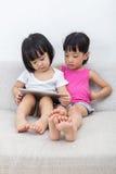 Petites soeurs chinoises asiatiques à l'aide du comprimé Image stock