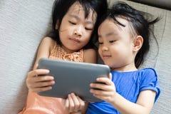 Petites soeurs chinoises asiatiques à l'aide du comprimé se trouvant sur le sofa Photo libre de droits