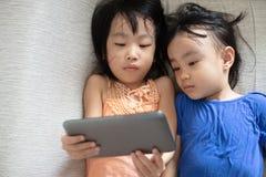Petites soeurs chinoises asiatiques à l'aide du comprimé se trouvant sur le sofa Images libres de droits