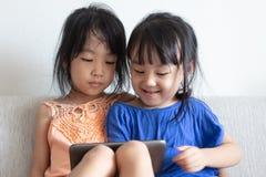 Petites soeurs chinoises asiatiques à l'aide du comprimé sur le sofa Image libre de droits
