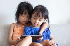 Petites soeurs chinoises asiatiques à l'aide du comprimé sur le sofa Images libres de droits