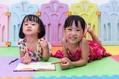 Petites soeurs chinoises asiatiques heureuses s'étendant sur la coloration de plancher Image stock