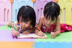 Petites soeurs chinoises asiatiques s'étendant sur la coloration de plancher Photo libre de droits