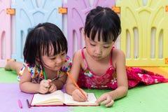 Petites soeurs chinoises asiatiques s'étendant sur la coloration de plancher Images libres de droits