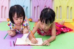 Petites soeurs chinoises asiatiques s'étendant sur la coloration de plancher Photo stock