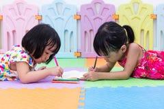 Petites soeurs chinoises asiatiques s'étendant sur la coloration de plancher Images stock