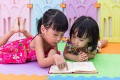 Petites soeurs chinoises asiatiques s'étendant sur la lecture de plancher Images stock