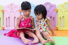 Petites soeurs chinoises asiatiques s'asseyant sur la lecture de plancher Images libres de droits