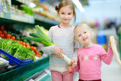 Petites soeurs choisissant des légumes dans un magasin de nourriture Photos stock