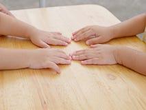 Petites soeurs de bébé plaçant leurs mains ensemble sur une table images libres de droits